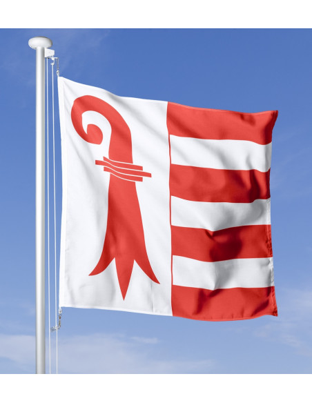 Le drapeau cantonal du Jura dans un vent fort contre un ciel bleu clair